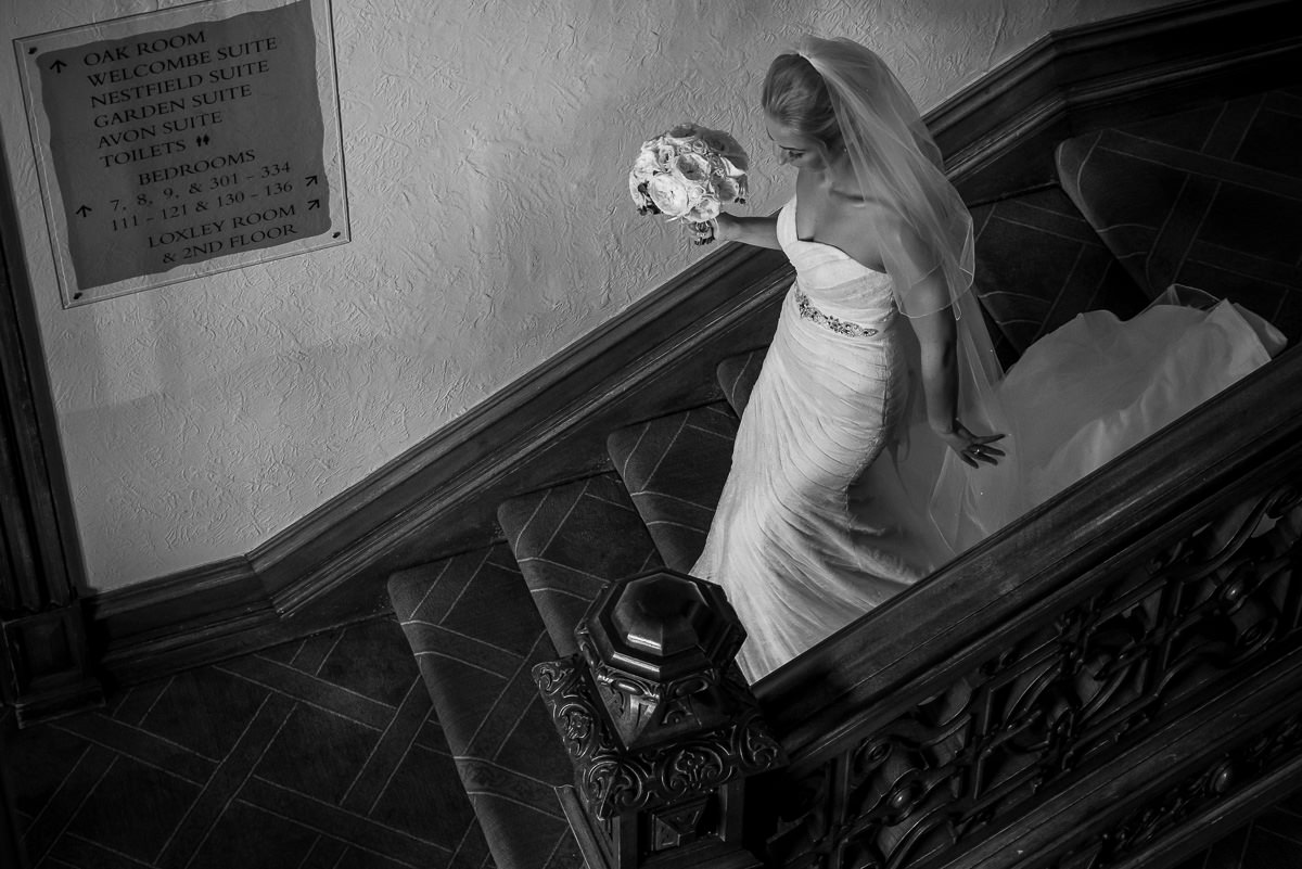 Bride makes her way down the grand staircase at The Welcombe Hotel in Stratford before her wedding ceremony.