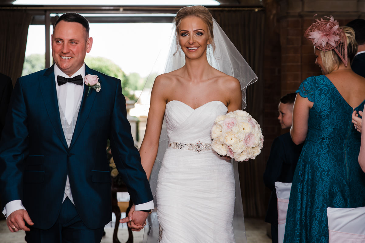 Newly married couple beam with smiles as they walk down the aisle after their ceremony at The Welcombe Hotel in Stratford.