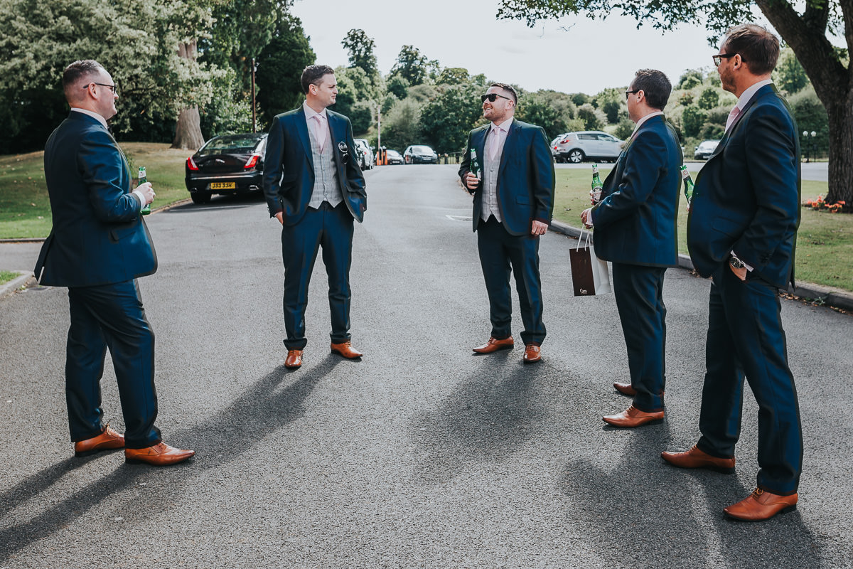 Groom and groomsmen dressed in blue suits, black bowties and brown shoes share a moment before the ceremony at the Welcombe Hotel in Stratford-upon-Avon.