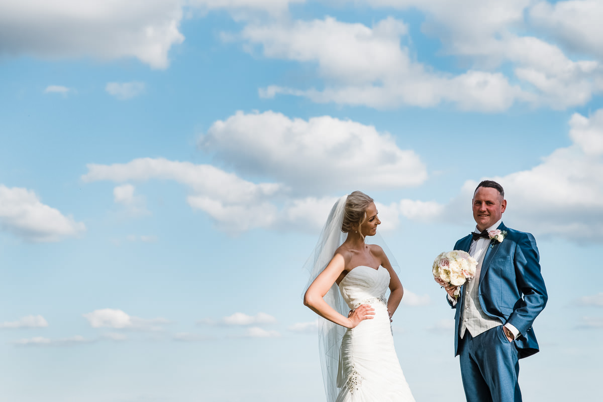 Bride and groom sharing a silly moment overlooking the golf course at the Welcombe Hotel and Spa.
