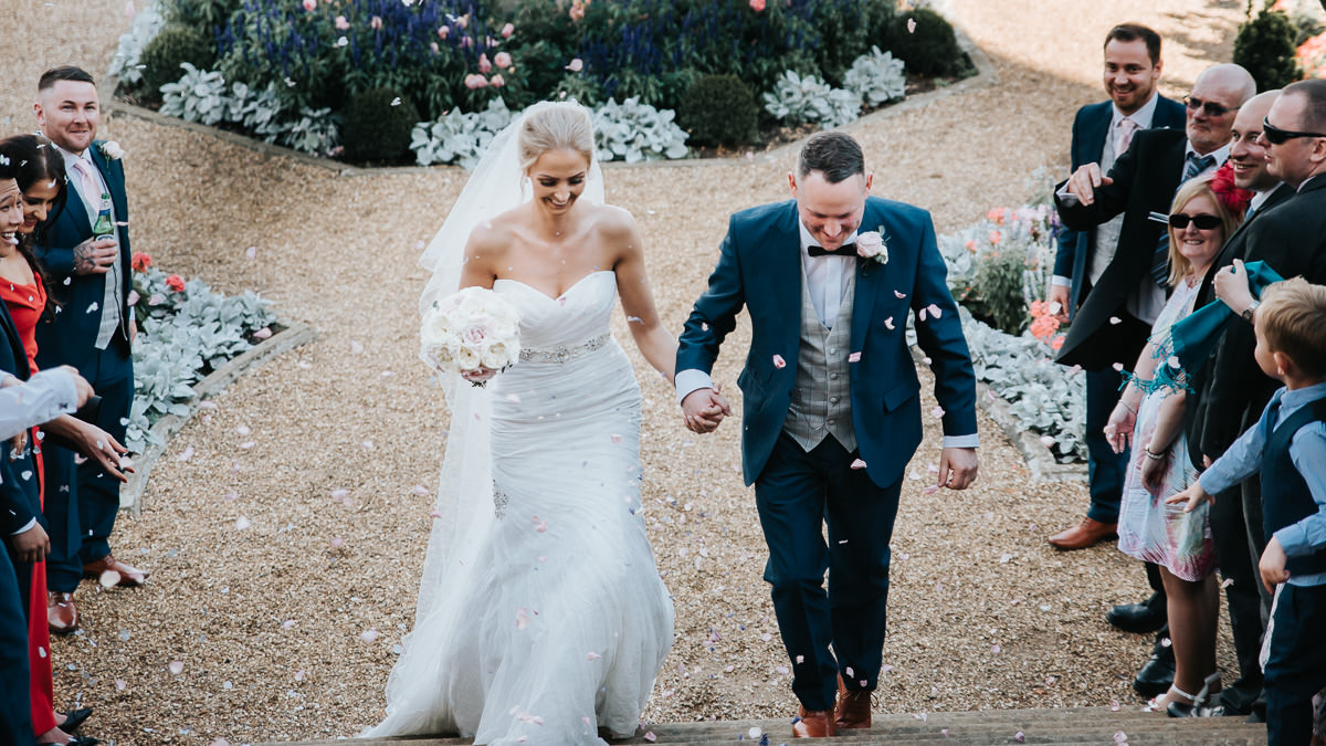Newlyweds enjoy their wedding day confetti on the grounds surrounding The Welcombe Hotel.