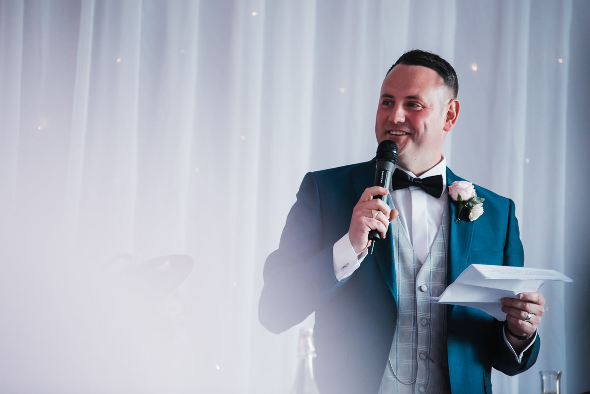 Groom gives his wedding speech in the banquet hall of The Welcombe Hotel.