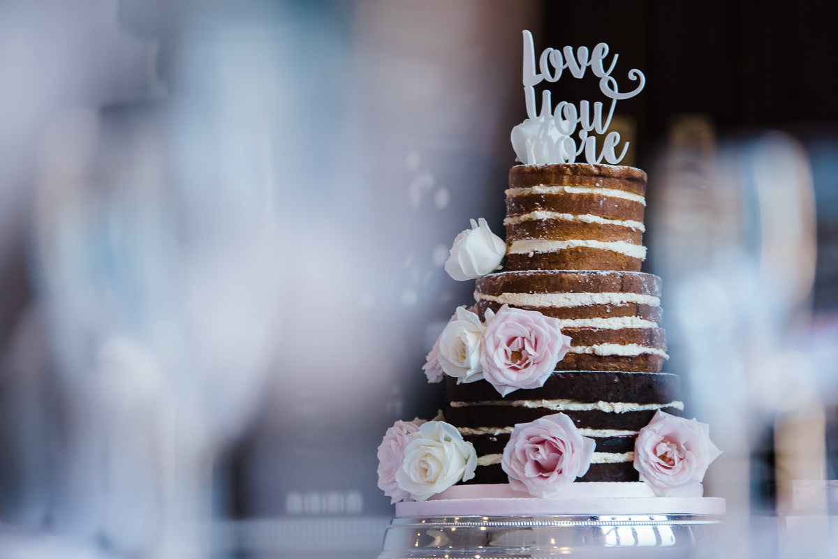 Naked cake with three tiers, decorated with pink roses and calligraphy cake topper at wedding at the Welcombe Hotel in Stratford.