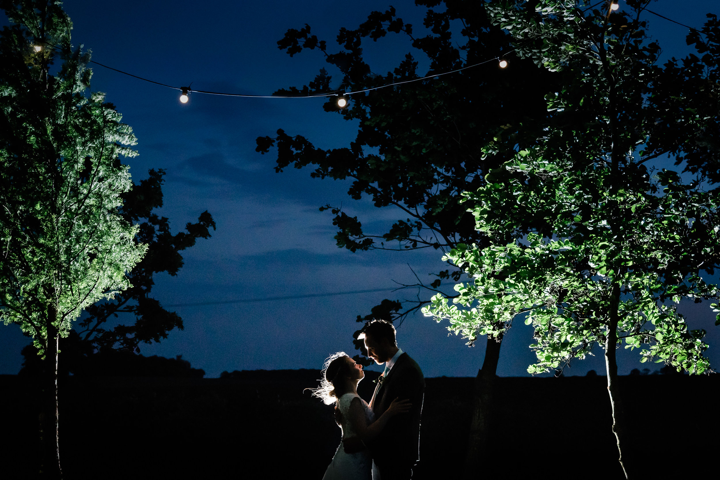 Faye and Matt sneak away from their wedding guests for a few moments under festoon lighting at dusk.