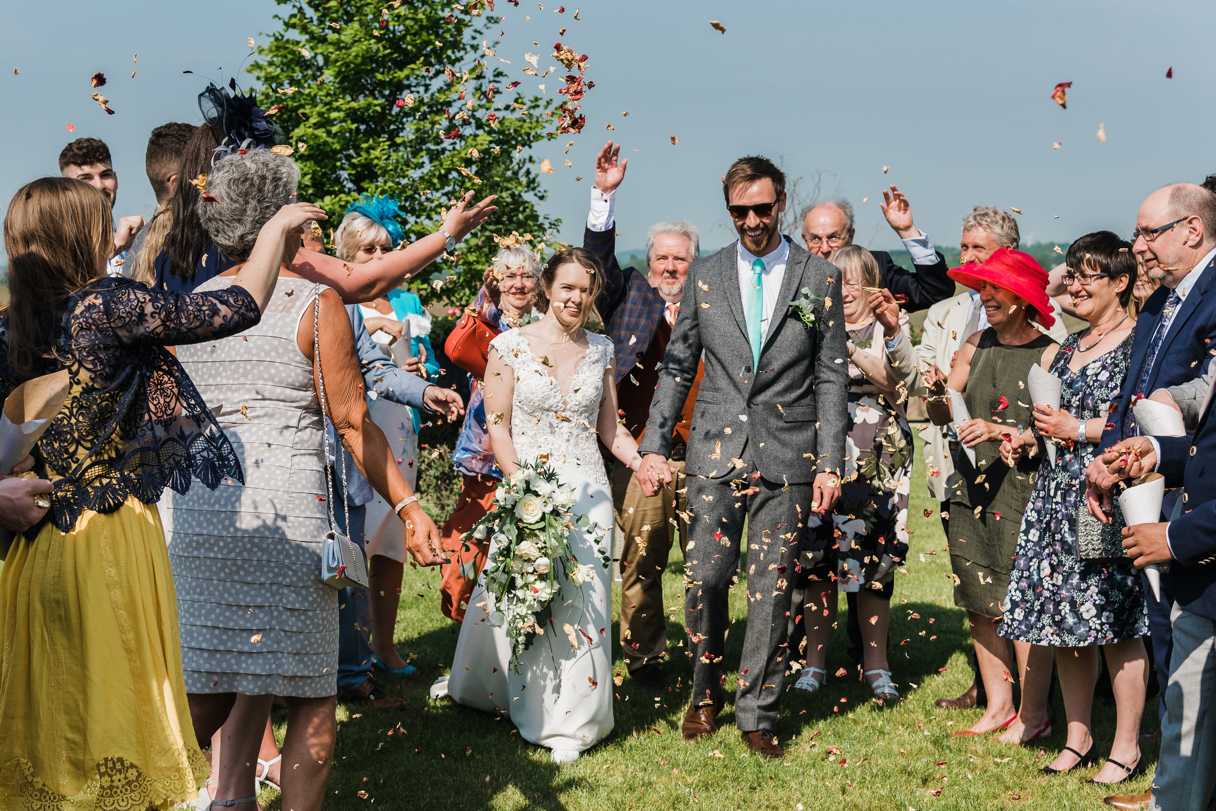 Stylish wedding couple enjoy confetti with dry petals in the summer sunshine on their wedding day in the Midlands.
