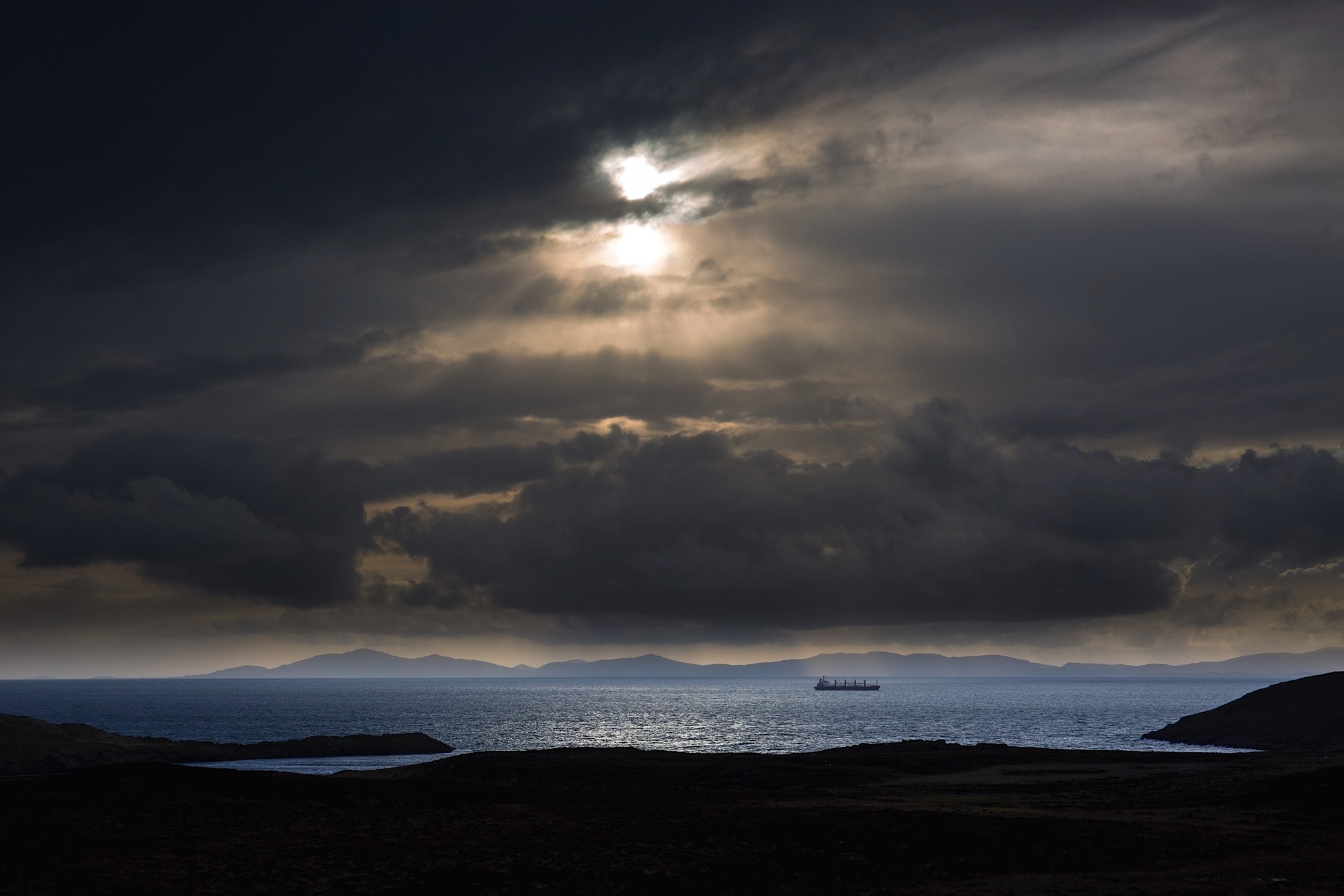 A ship passes through the dramatic light of Duntulm Bay