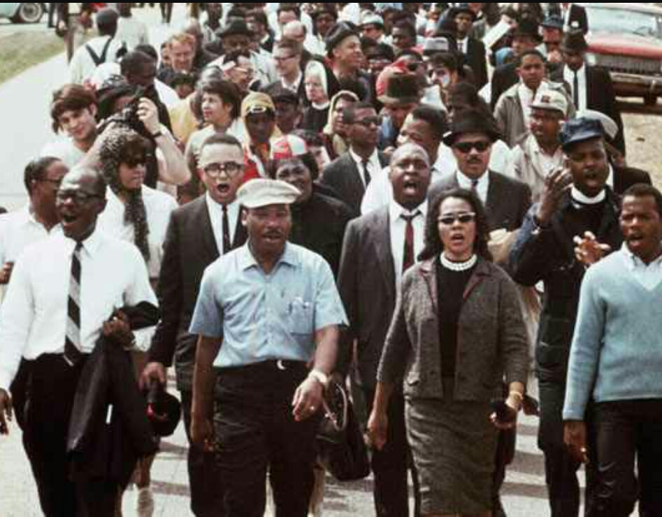 Above is an original historic photo, from the March on Selma. To the right of him is his beautiful wife, Coretta Scott King.