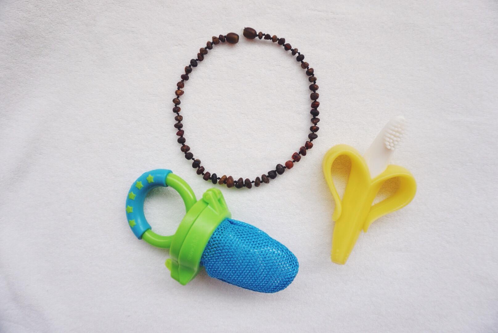 (clockwise) Amber teething necklace, Baby Banana Infant Teething Toothbrush, Munchkin Fresh Food Feeder.