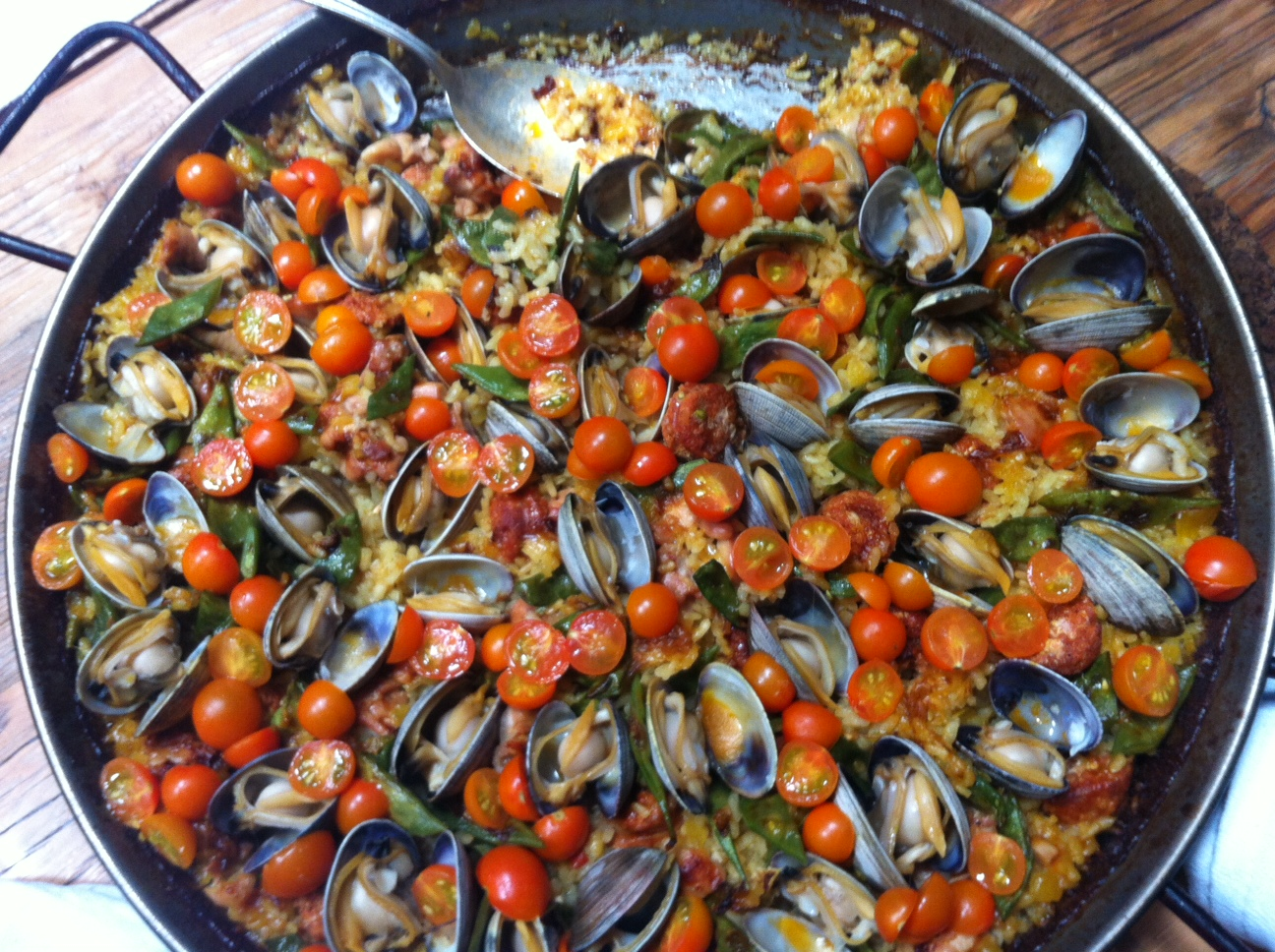 Large skillet dish with clams and cherry tomatoes