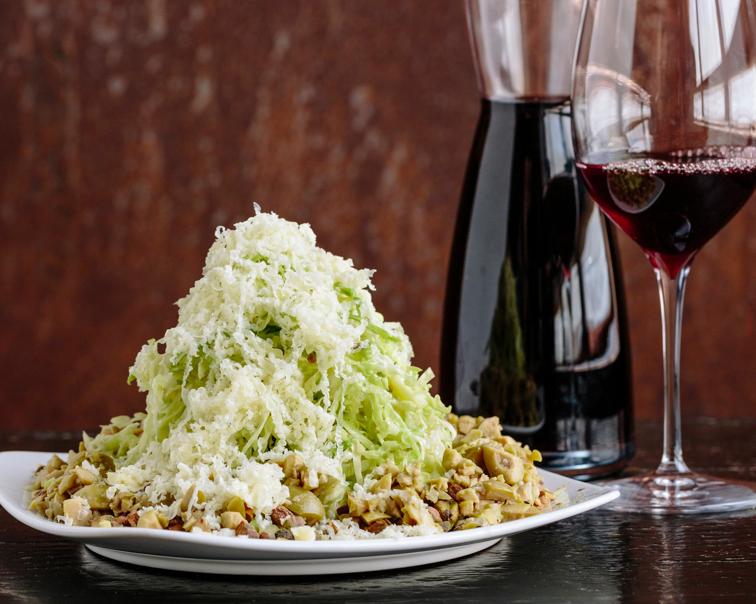 Meal topped with lettuce and cheese by a glass of red wine