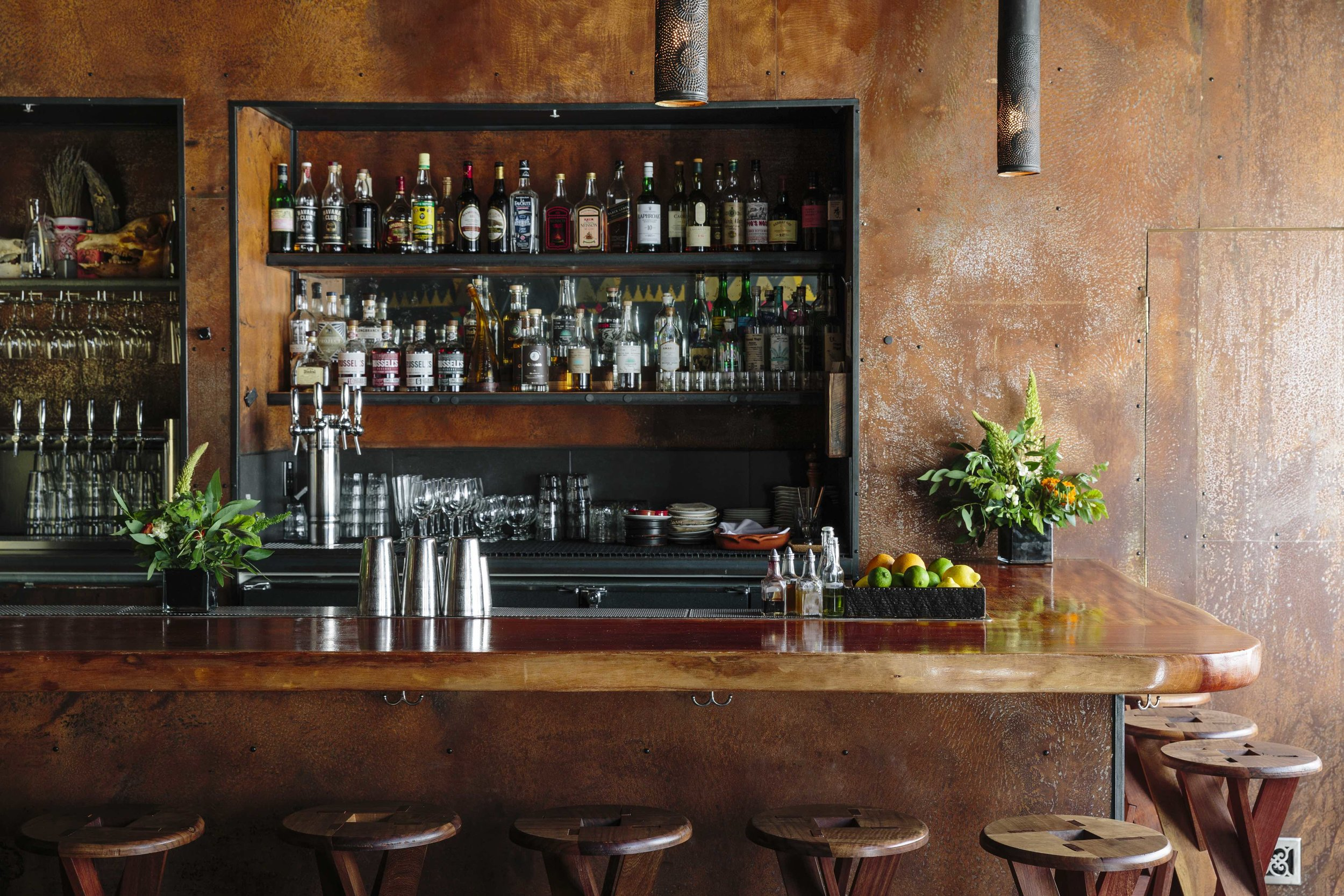 Duende bar with alcohol bottles, cups and plants