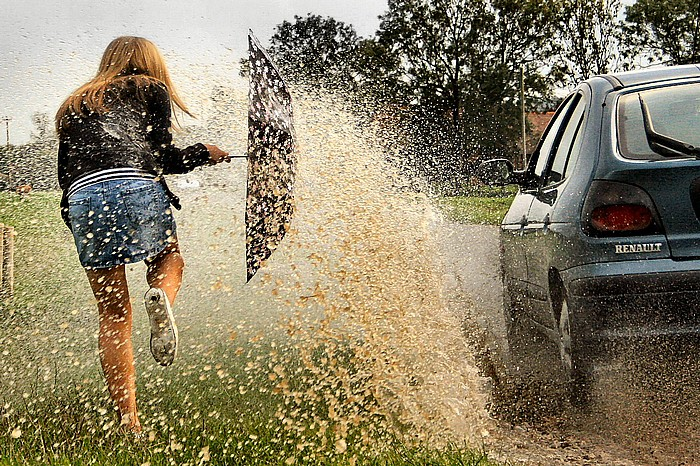 A woman holds an umbrella to try to block a gush of muddy water showering her from a passing car. Creative Commons image by Brett Jordan.