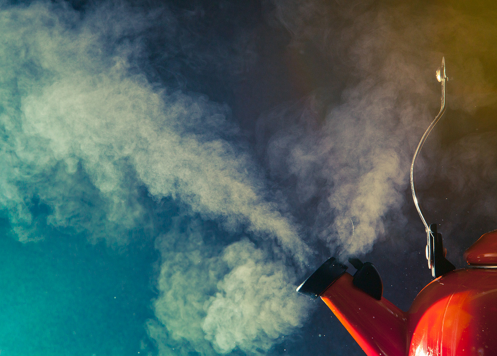 Image of a red tea kettle blowing clouds of steam - Creative Commons image by Benjamin Lehman