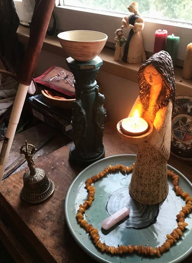 Image by Arie Farnam - An altar for the goddess Brigid with a stature holding a lit candle surrounded by a string of amber beads and a rose quartz crystal in the foreground. In the background there is a pedestal with goddess carvings and an offering bowl at the top. Candles and a corn-husk doll sit on a window sill. To the left a white cane with a brown wood handle leans against the altar over a brass bell.
