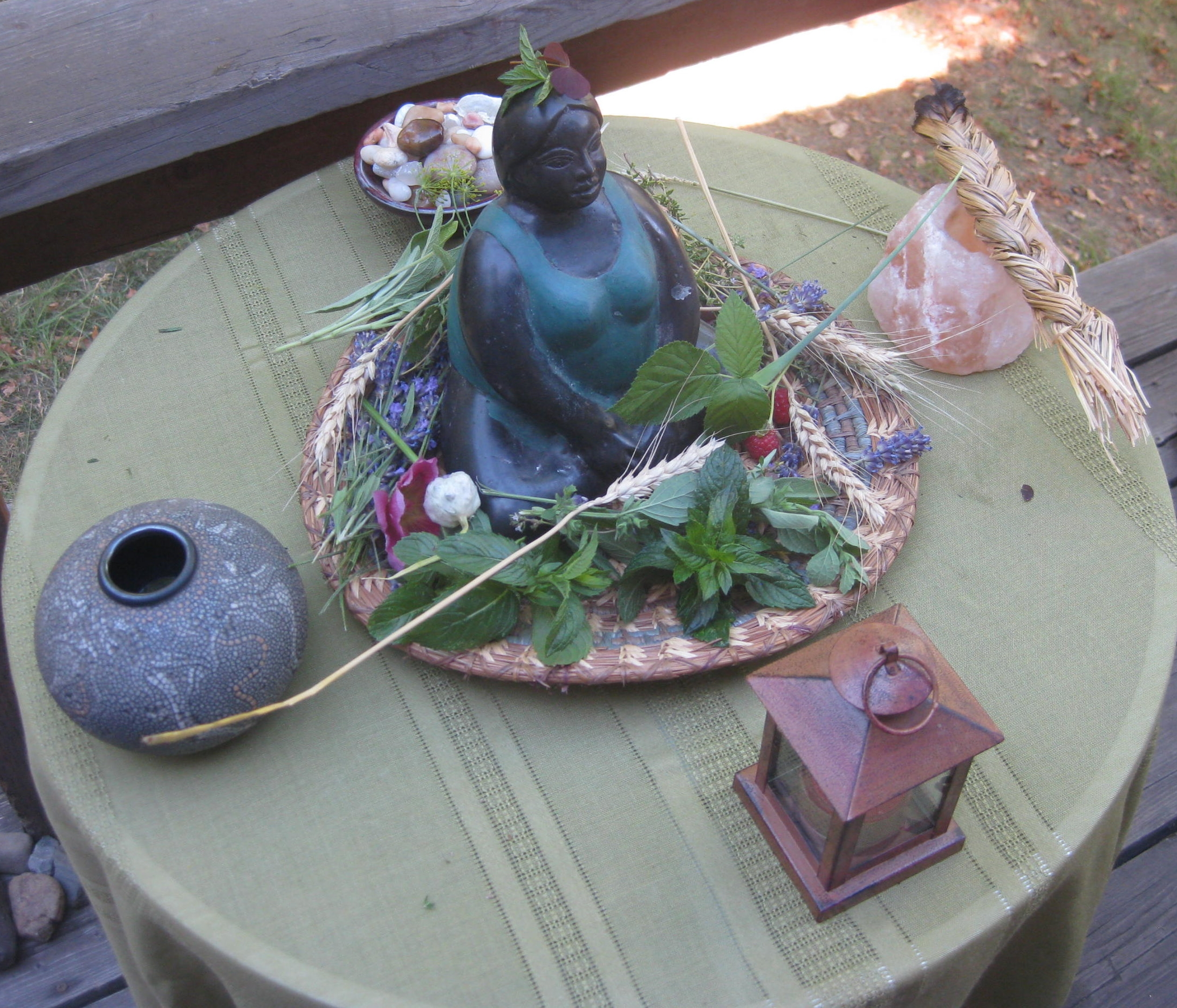 Image by Arie Farnam - A simple altar is set up on an outdoor table. In the center there is a blue-black goddess stature surrounded by fresh leaves, flowers and stalks of wheat. In front of her there is a small lantern for a candle. Behind her there is a small bowl filled with stones. On the left there is a gourd-shaped water container and on the right there is a braided sweet grass smudge stick on a candle holder.