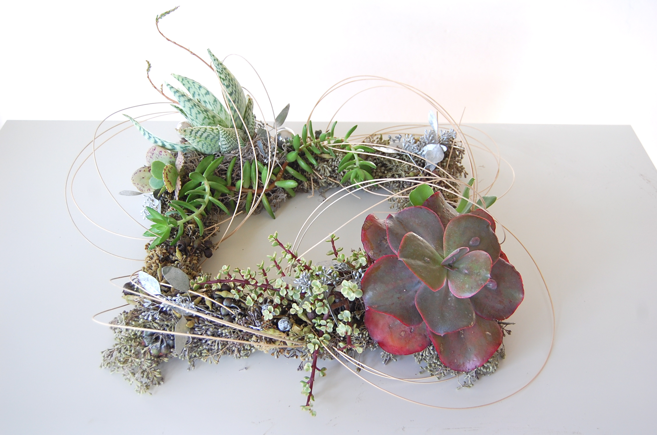 "SINGLE SQUARE WREATH/CENTERPIECE   16""w  – $120."