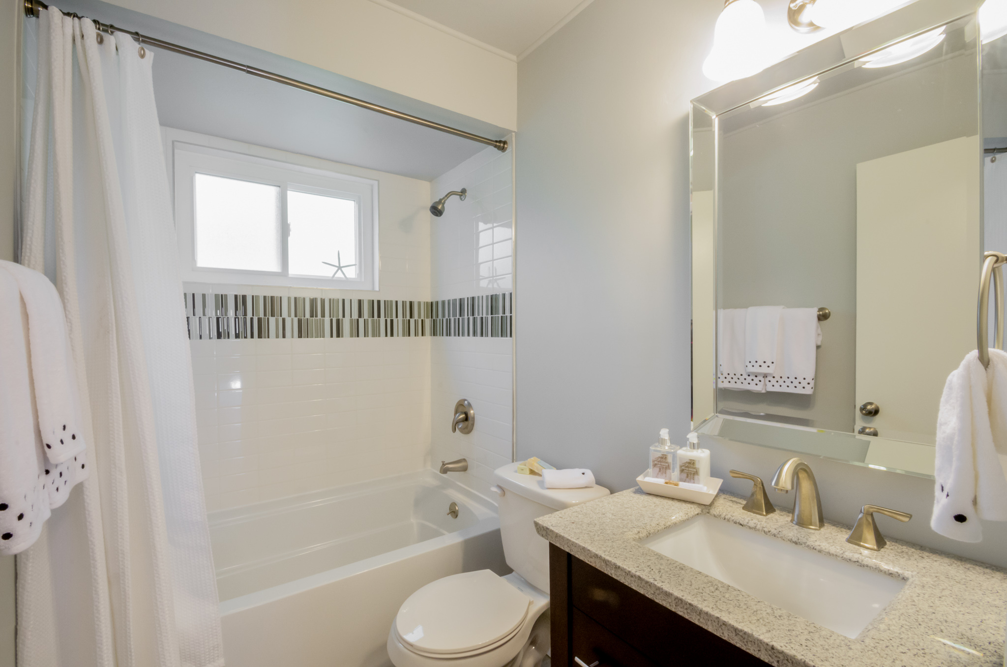 Grandview Bathroom After with white subway tile, soaking tub, new toilet, vanity, and fixtures.
