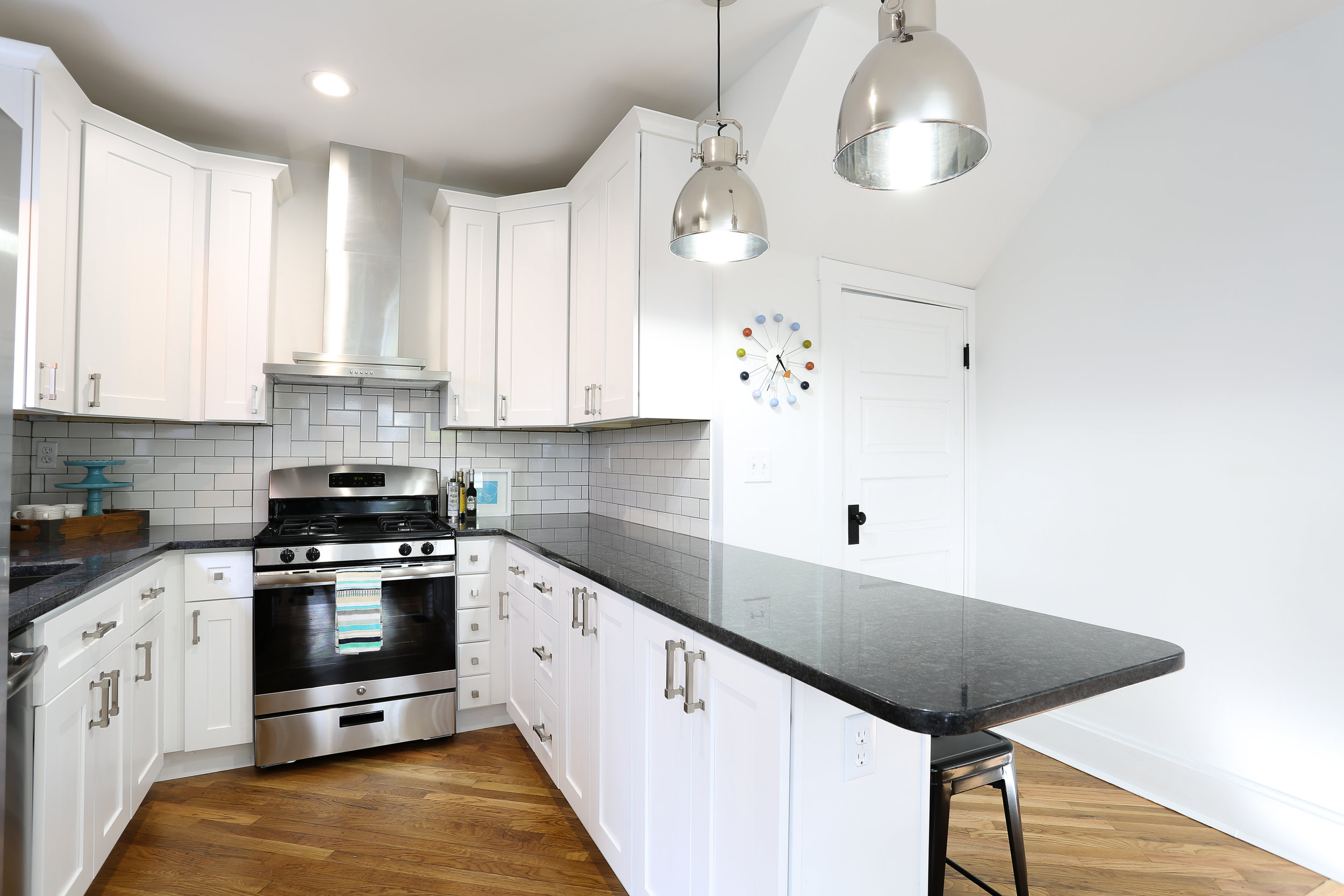 Schoolhouse industrial black and white kitchen with herringbone subway tile