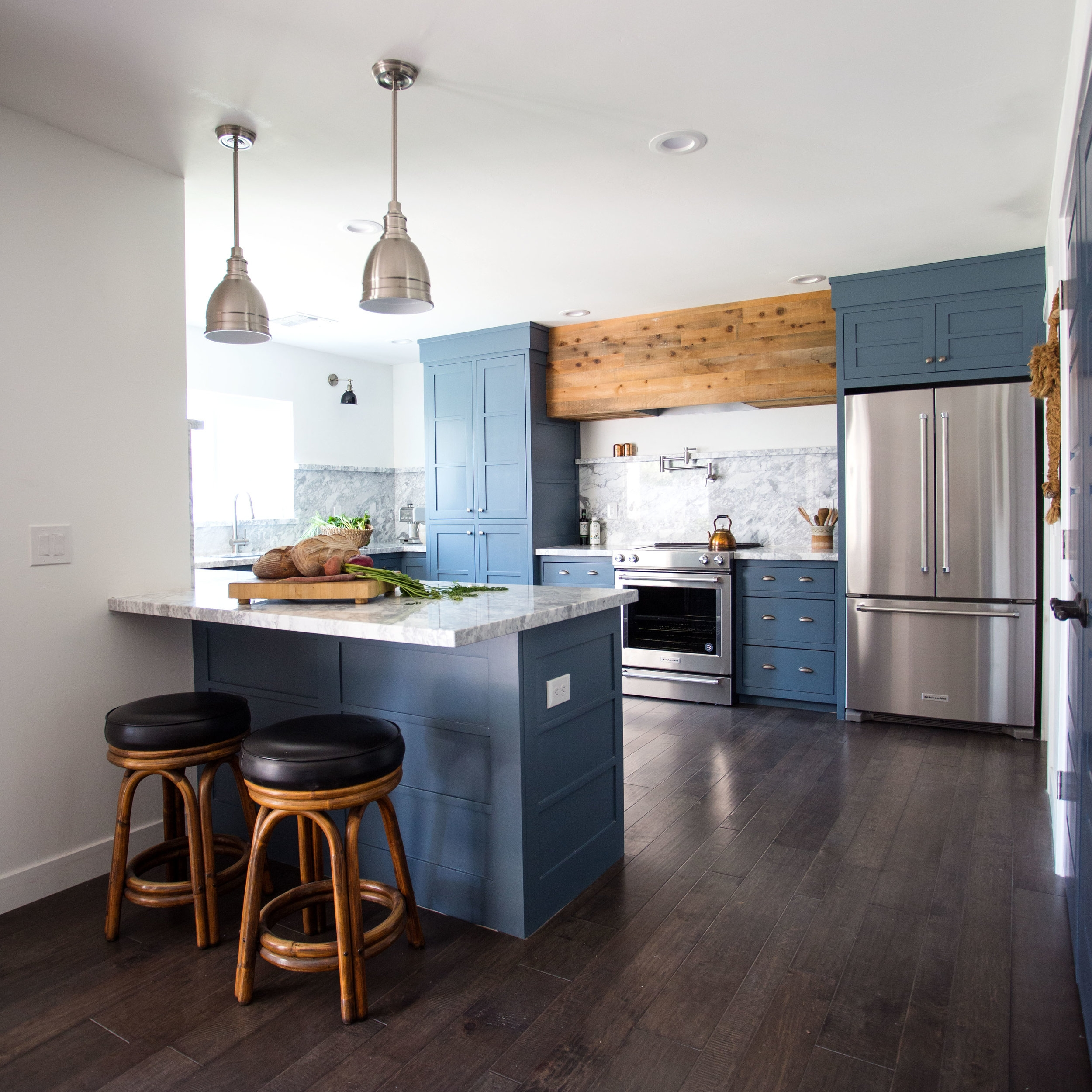 Blue Farmhouse Style Kitchen with marble counters and barnwood hood