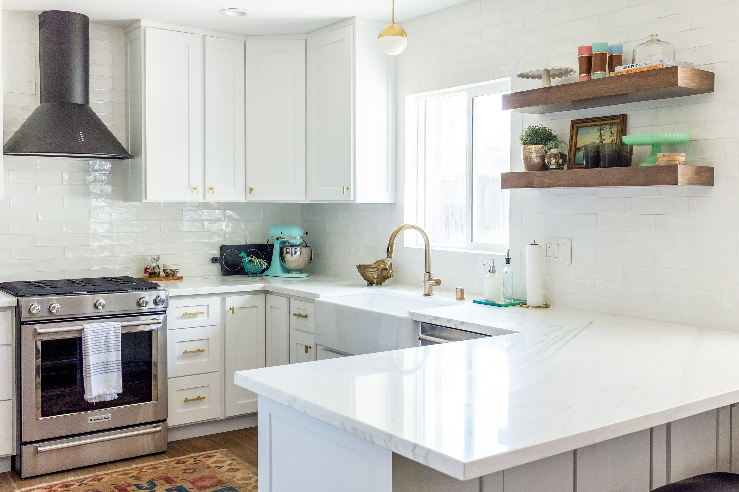 Retro White Shaker Kitchen with Black and Stainless Appliances, floating shelves, mid century modern lighting and long subway tile backsplash