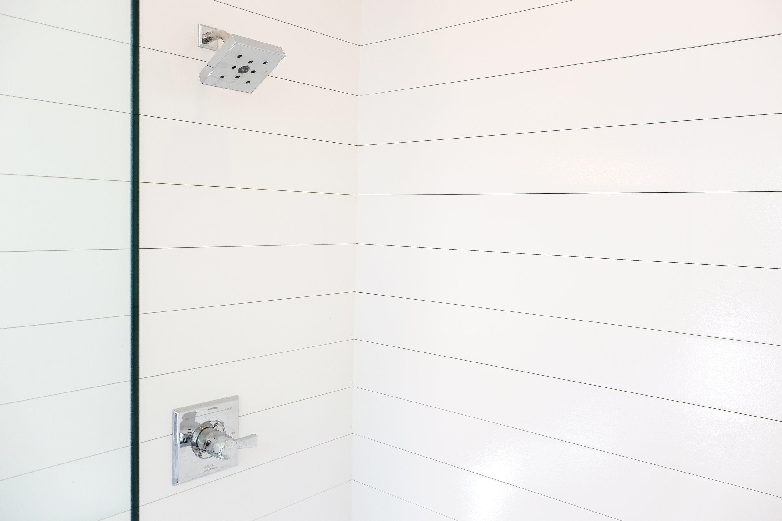 Shiplap shower with chrome Delta faucet