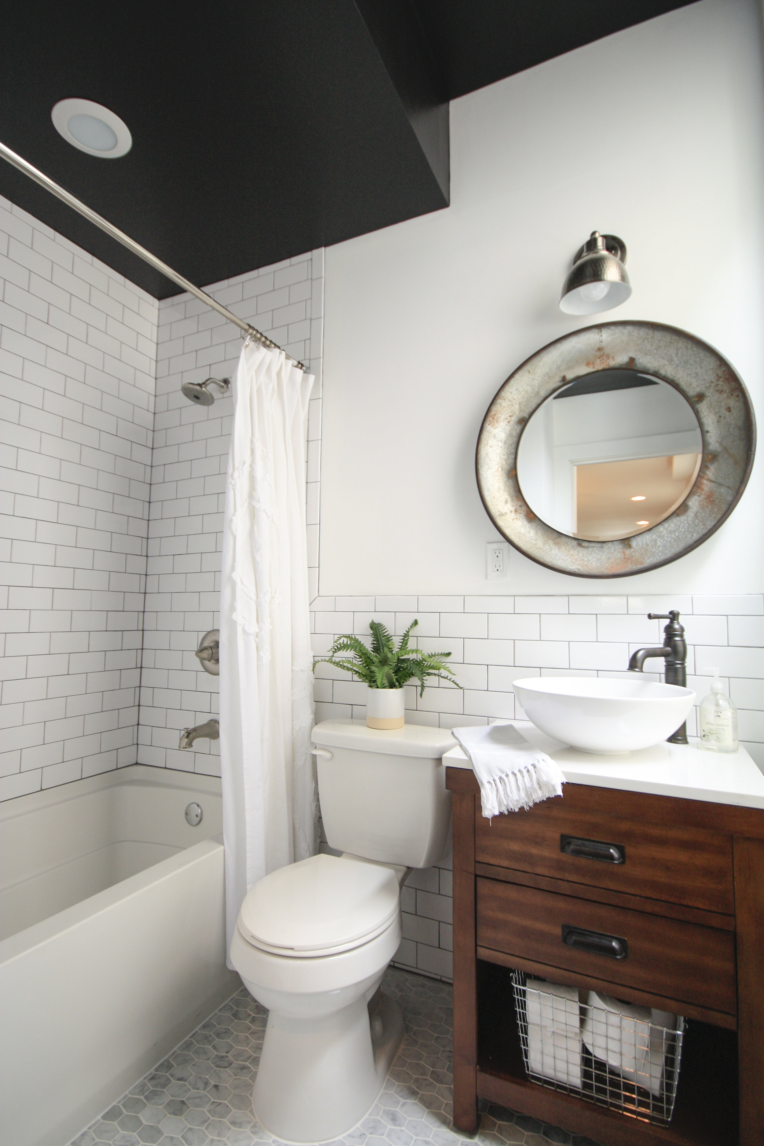 Black ceiling with white subway tile and dark grout