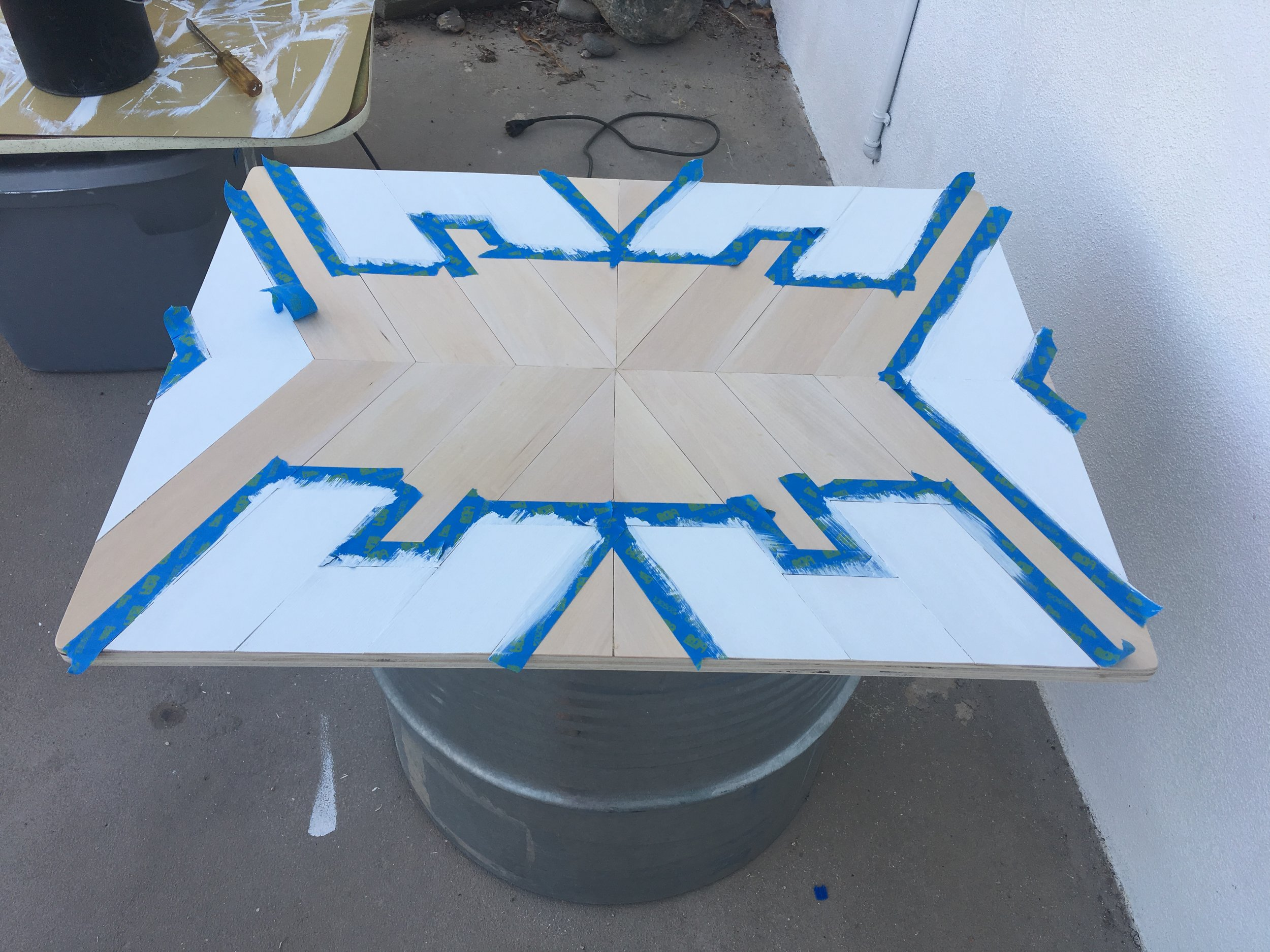 Taping off the pattern and painting geometric table