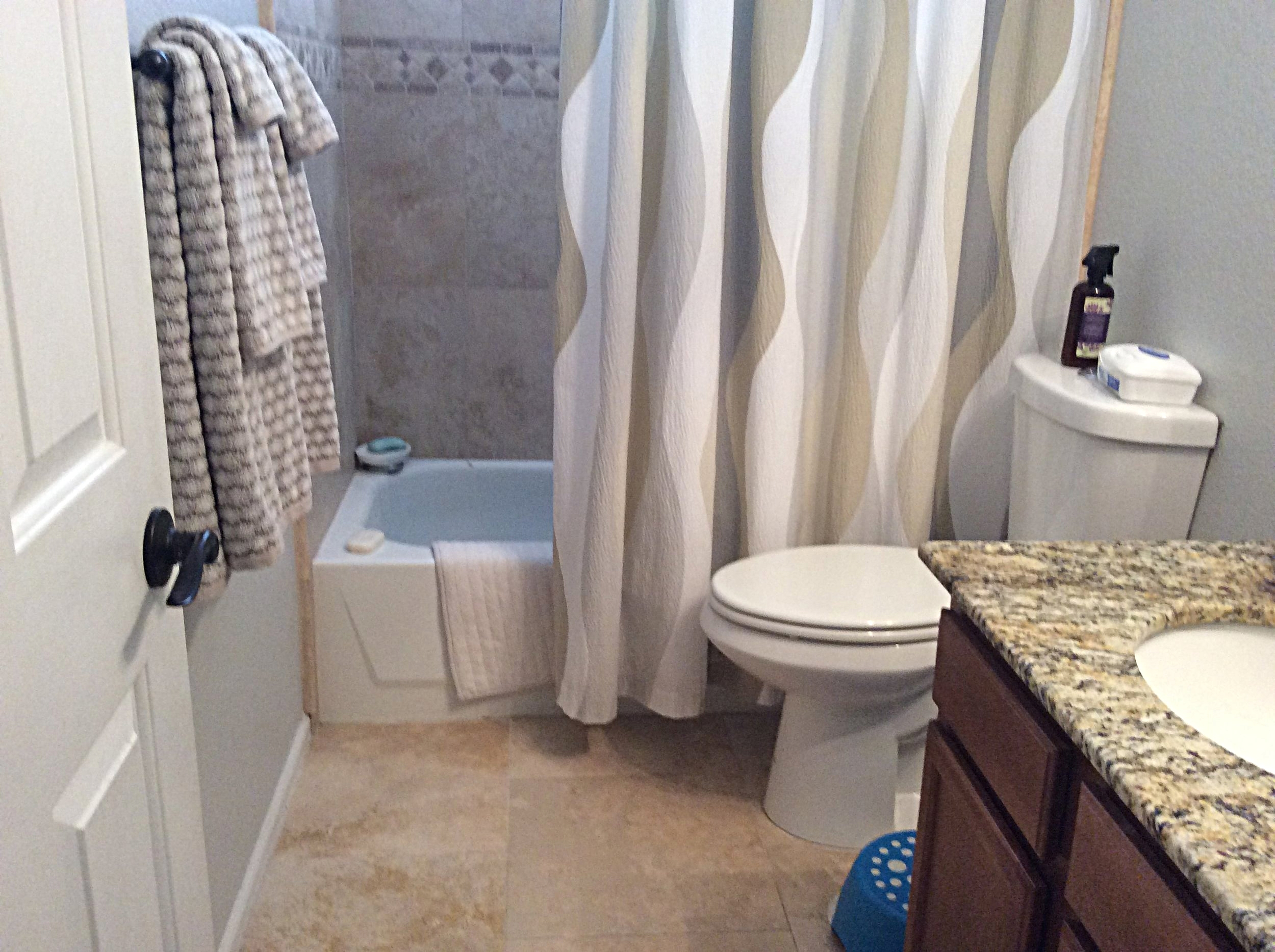 Travertine with gray/blue walls and shower curtain