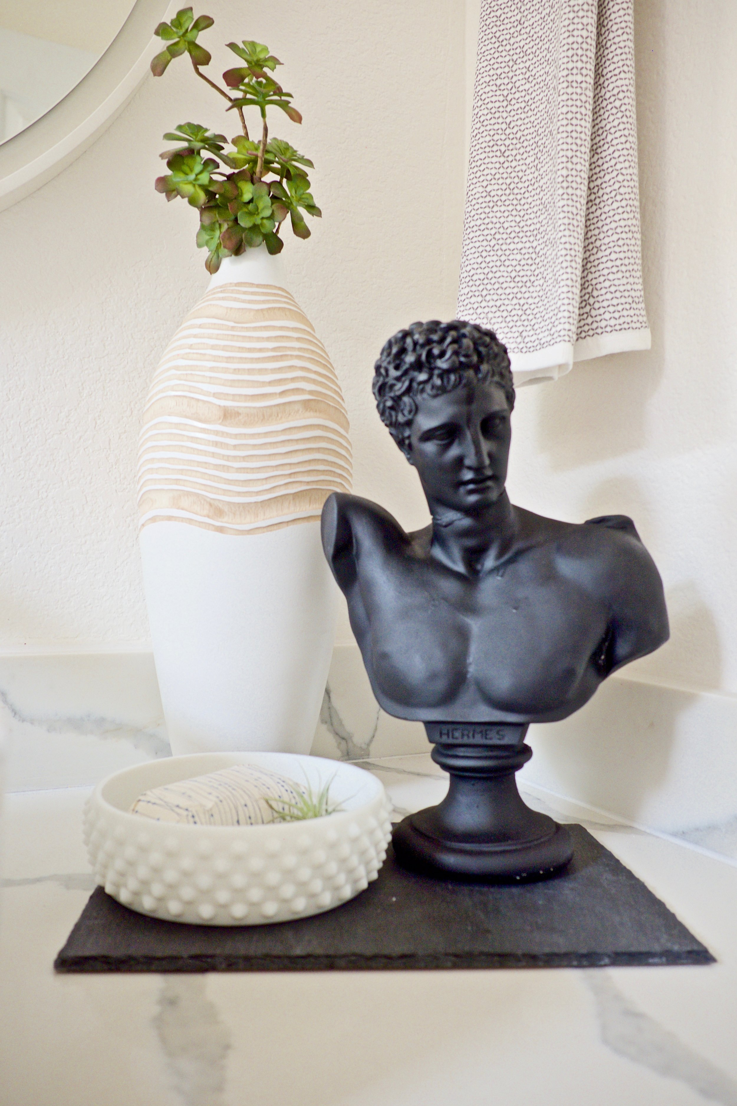 Bust and cheese tray make a great bathroom