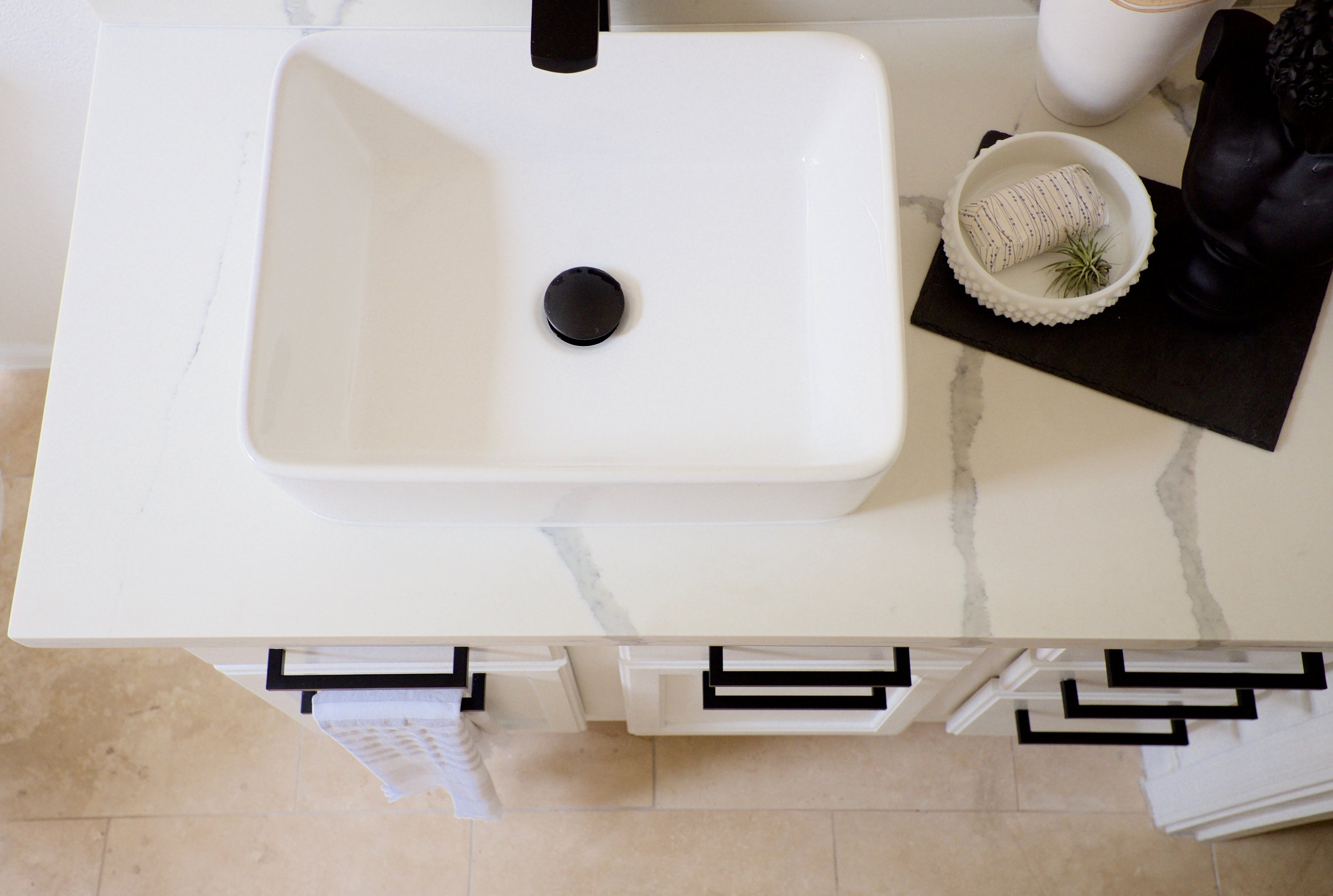 Vessel sink and quartz counter with black faucet in bathroom renovation