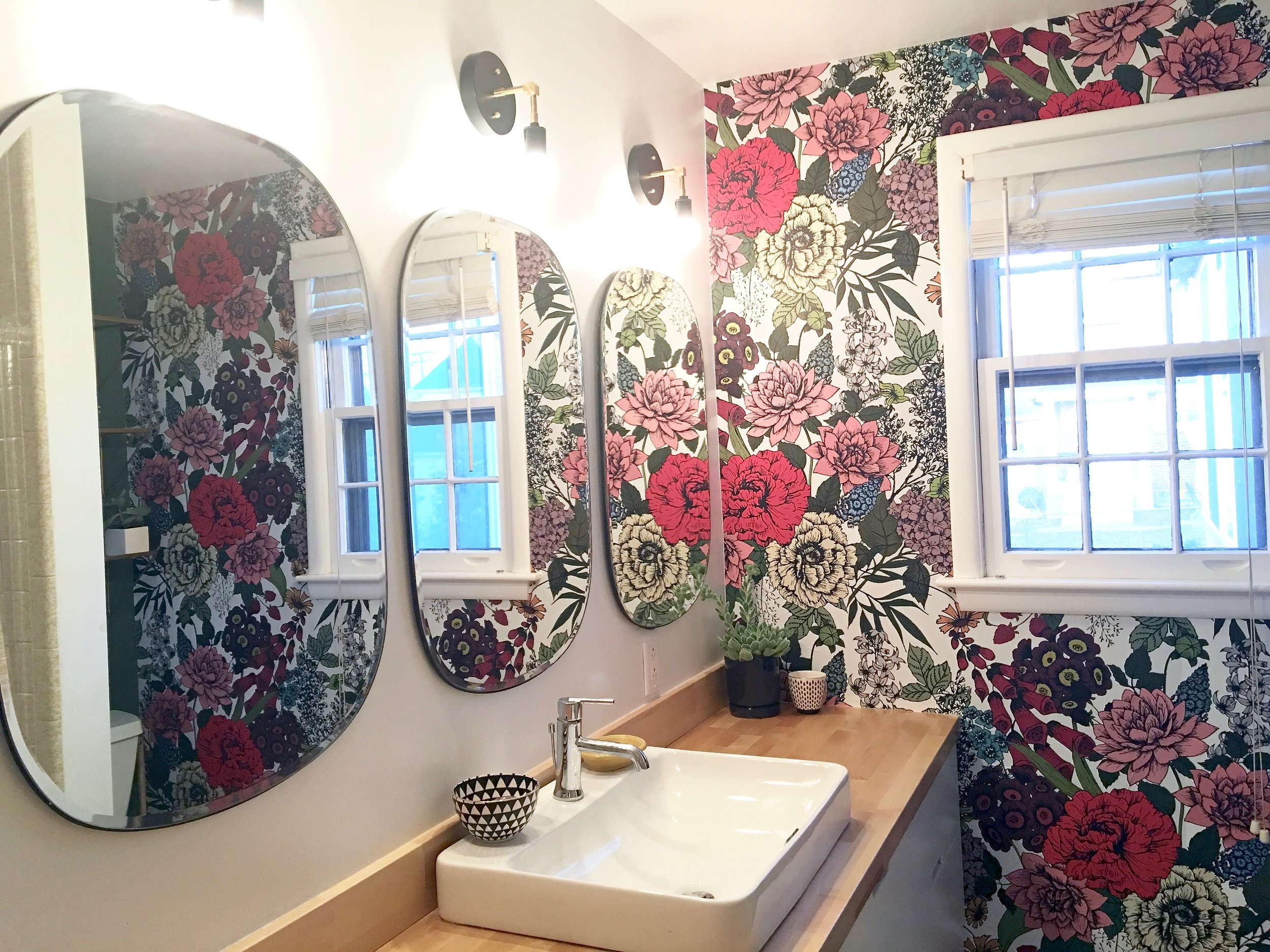 Rectangular mirrors and sconces in wallpaper accent wall bathroom