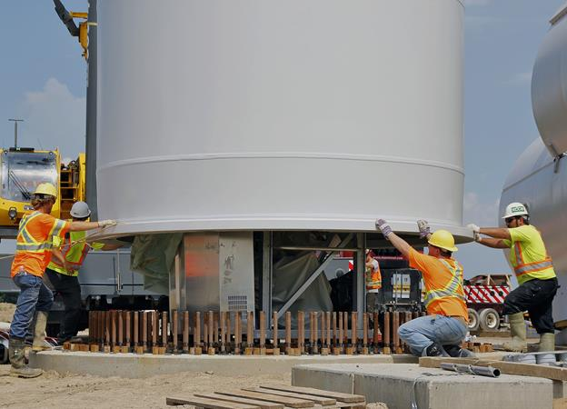 Source   :  ReNews 'Champagne Flows at South Kent '. Attaching base section of wind tower to foundation
