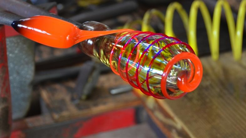 Threading hot glass to the piece in making a cup.
