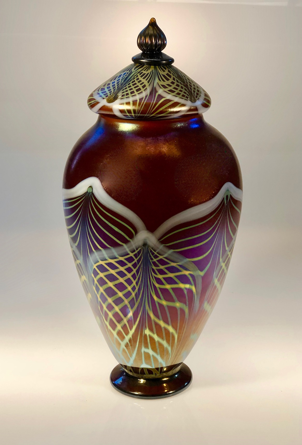 "Amber Lidded Jar with Iridized surface and a double decorated Lace pattern with lid. 7"" w x 16"" h Old school decorating techniques with hot glass. 60's studio movement into today. 2019 Strini Art Glass."
