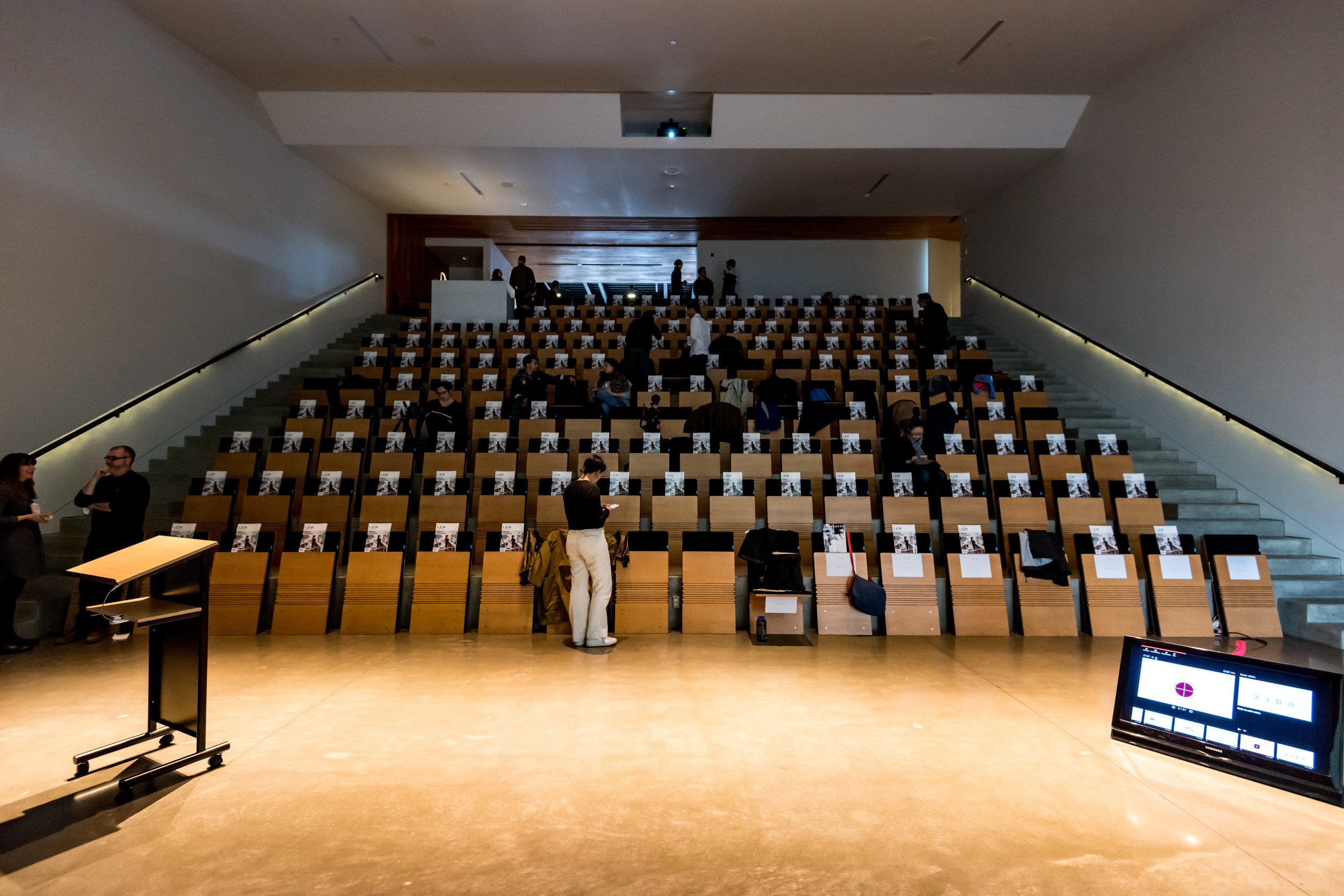The audience trickling into Ziba's auditorium and finding their seats