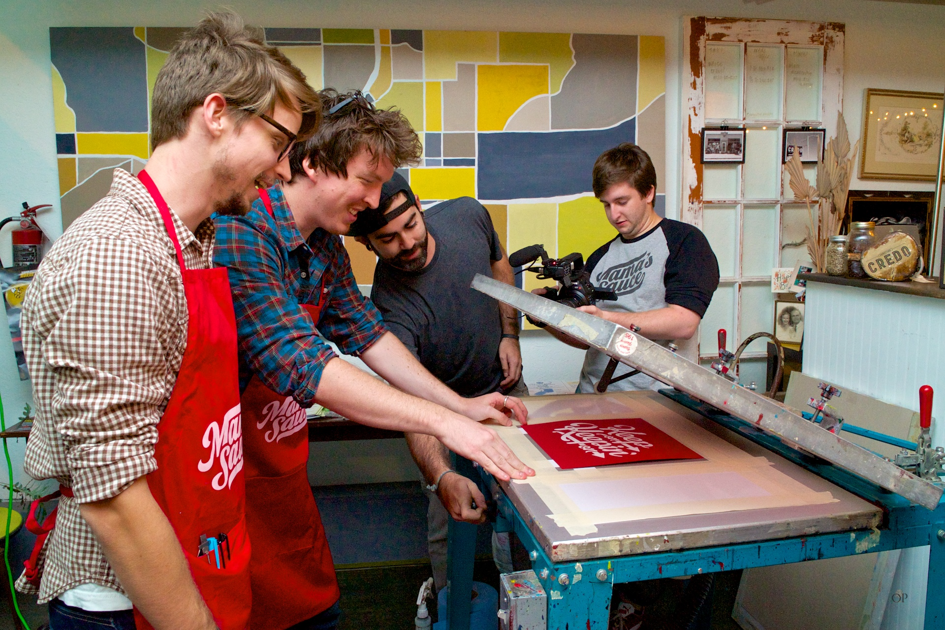 Guest Professor  55 Hi's  hand-pulling a screen print at an intern community event.