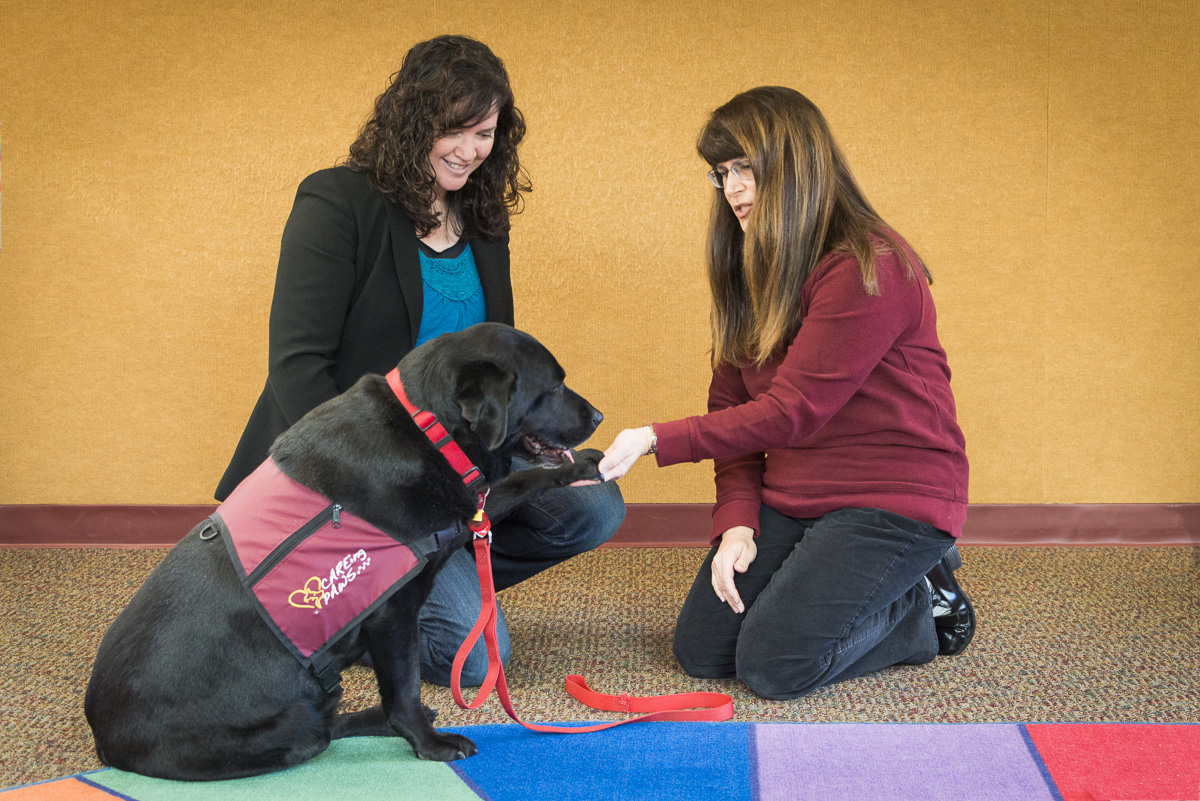 Melissa Saul, founder of CAREing Paws, shakes hands with her dog Gina at the Peachtree City, GA library.