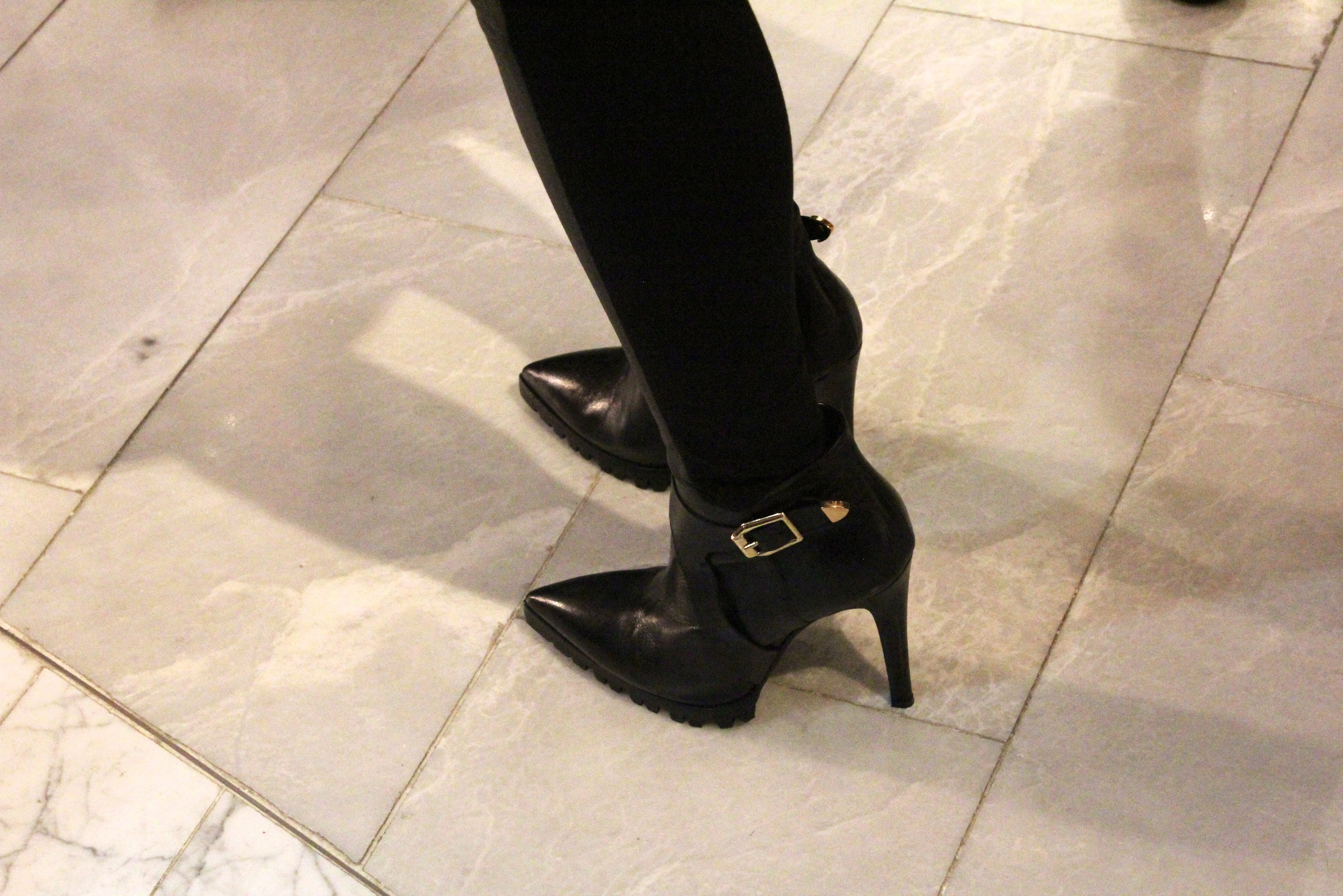 Black leather boots with golden buckle