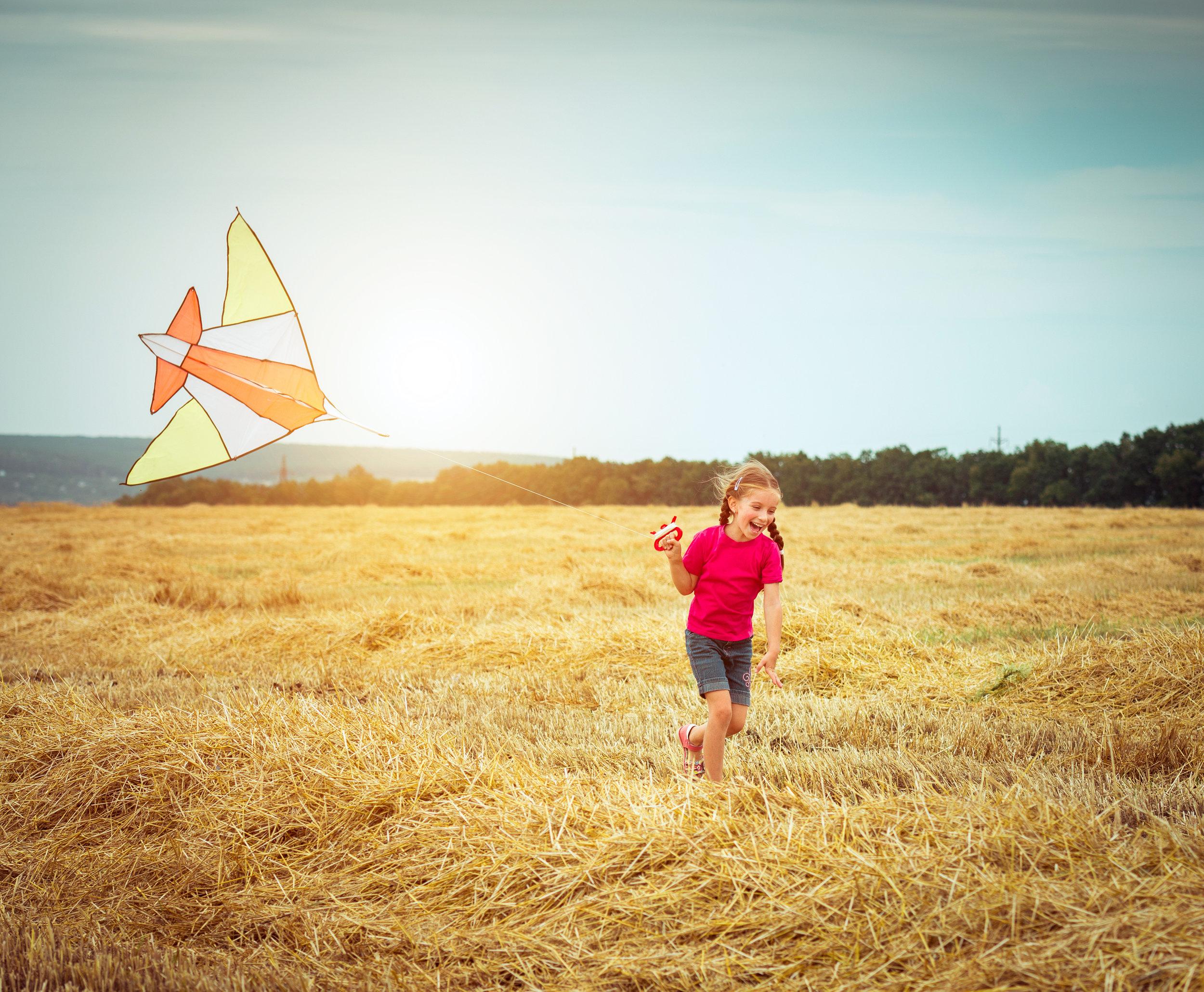 bigstock-happy-little-girl-witha-kite-i-74487529.jpg