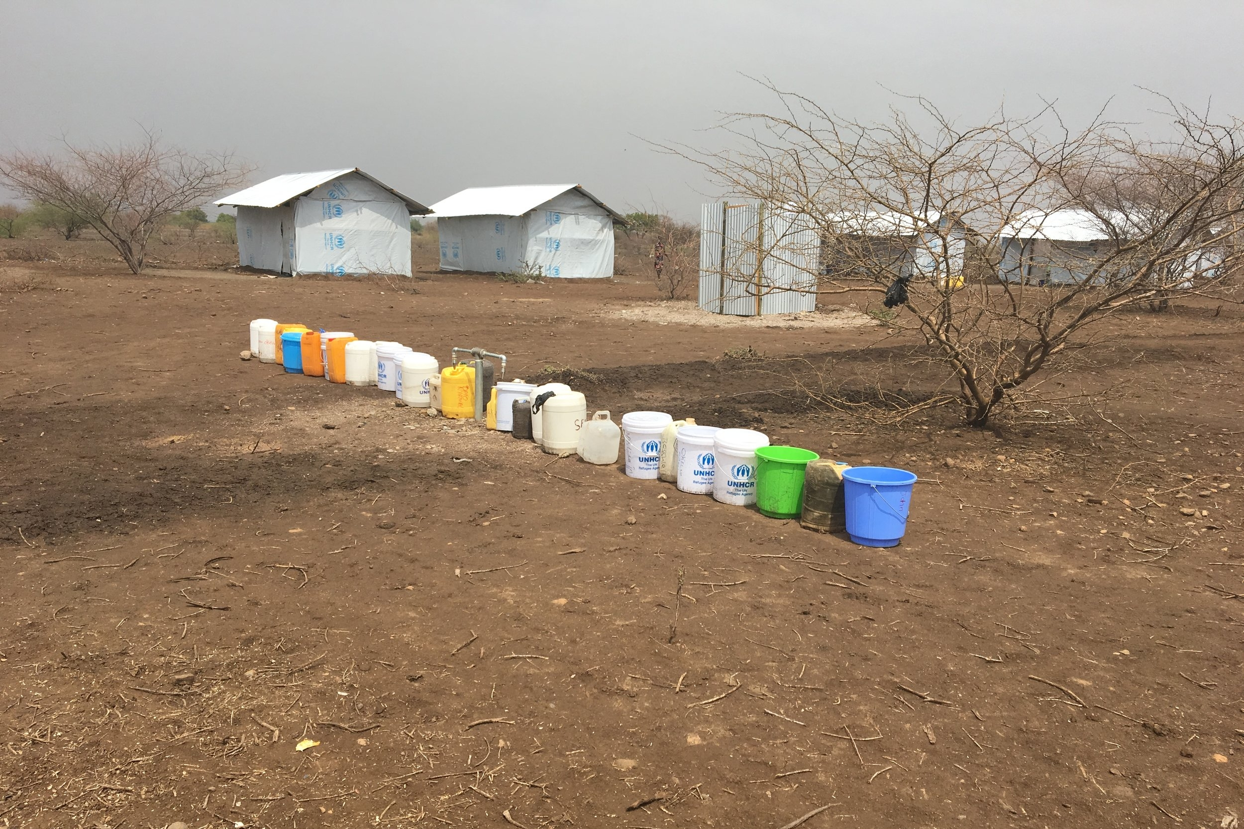 Jerry cans queued at water tap in Kalobeyei ©FilmAid/OCallaghan