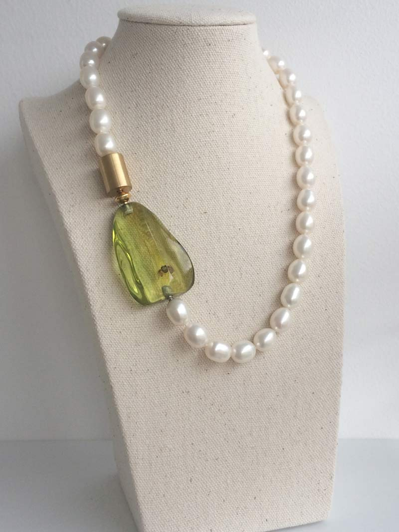 Cream freshwater pearl necklace with gold cylinder and green amber clasps connected by a gold adaptor