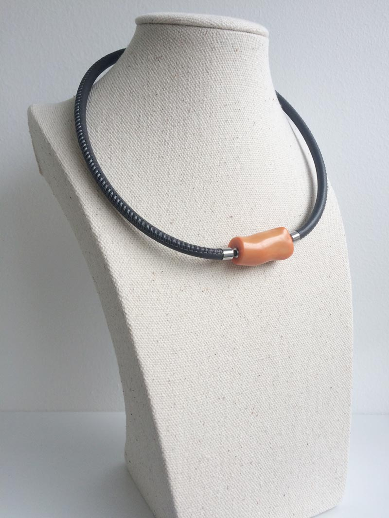 Grey leather necklace with orange bamboo coral feature clasp