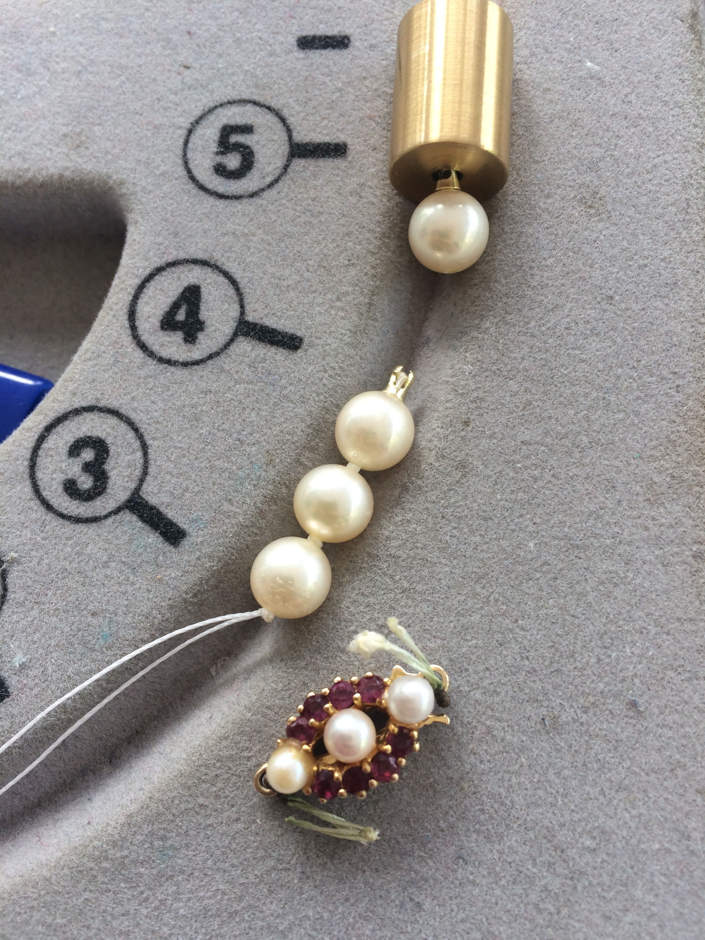 Last pearl waiting in the gold cylinder clasp