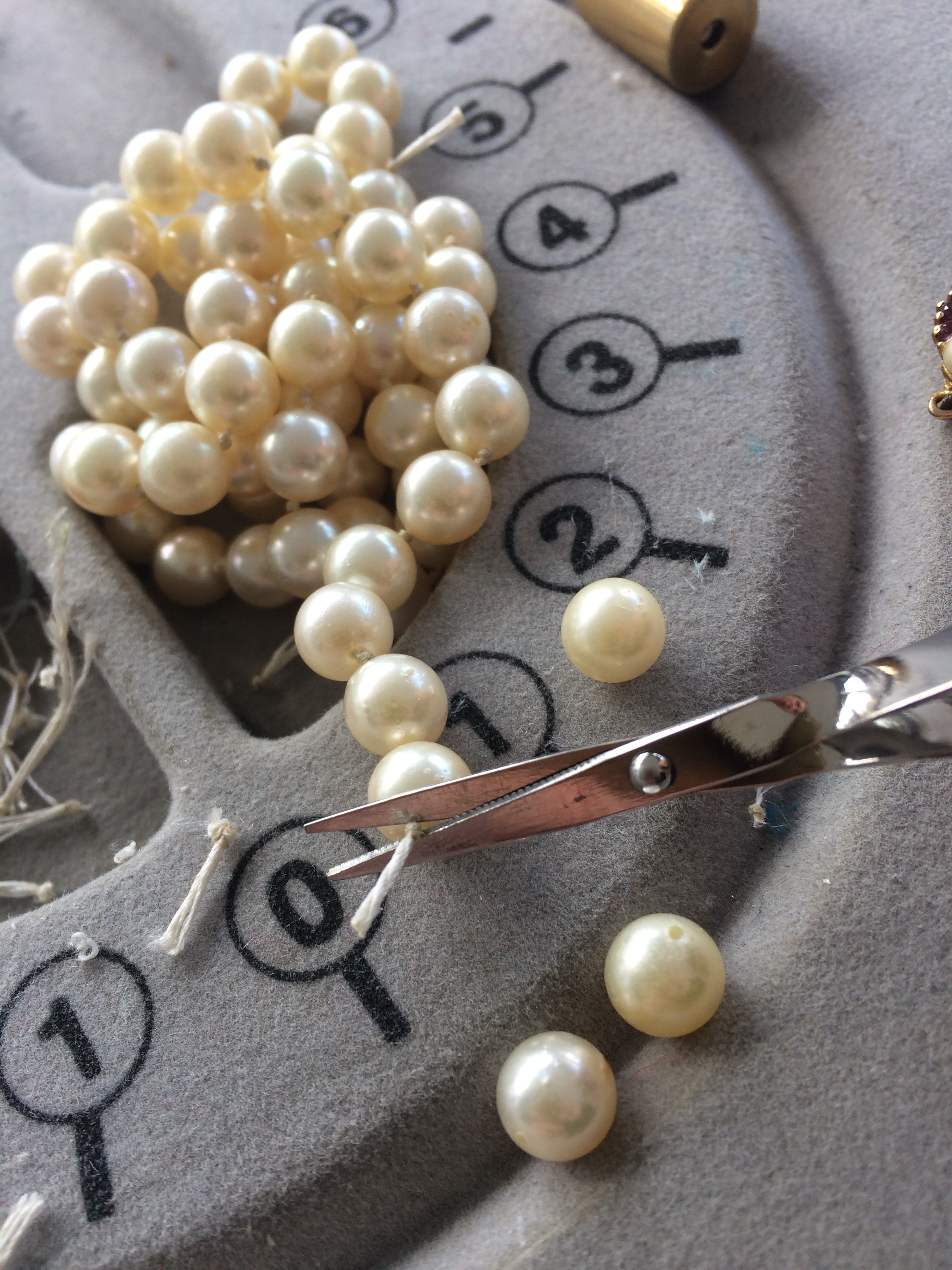 Cutting each knot to remove the individual pearls