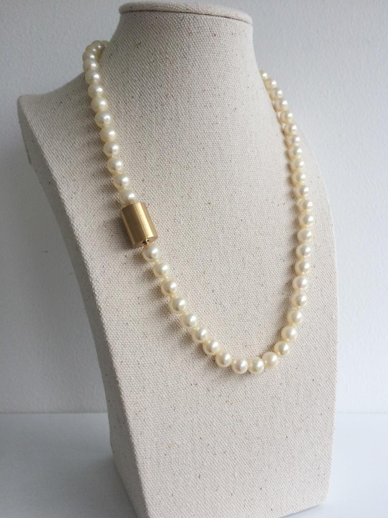 The finished pearls restrung with knots and 14ct yellow gold bayonet fittings closed with an interchangeable gold cylinder clasp