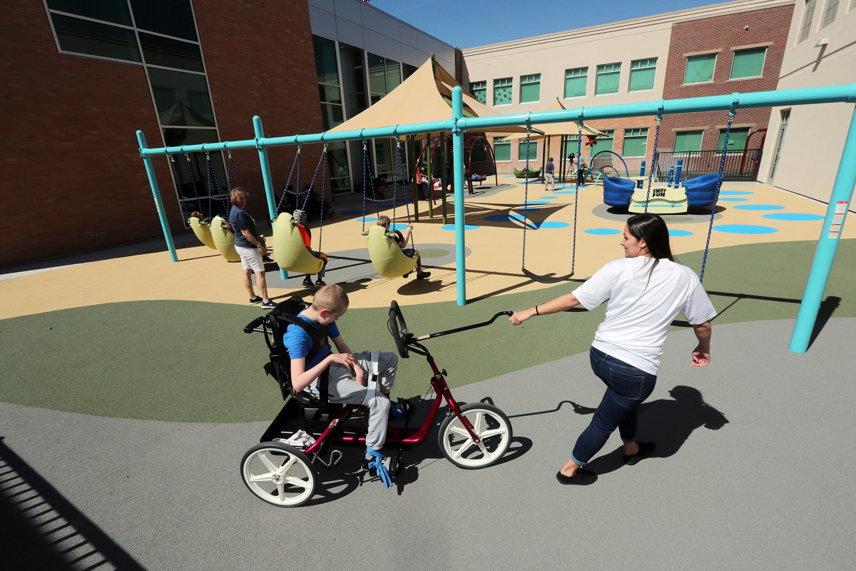 Christian Knudson rides a bike with the help of Angel Randles as students at the Kauri Sue Hamilton School in Riverton enjoy their new playground on Tuesday, May 14, 2019. - Scott G Winterton, Deseret News