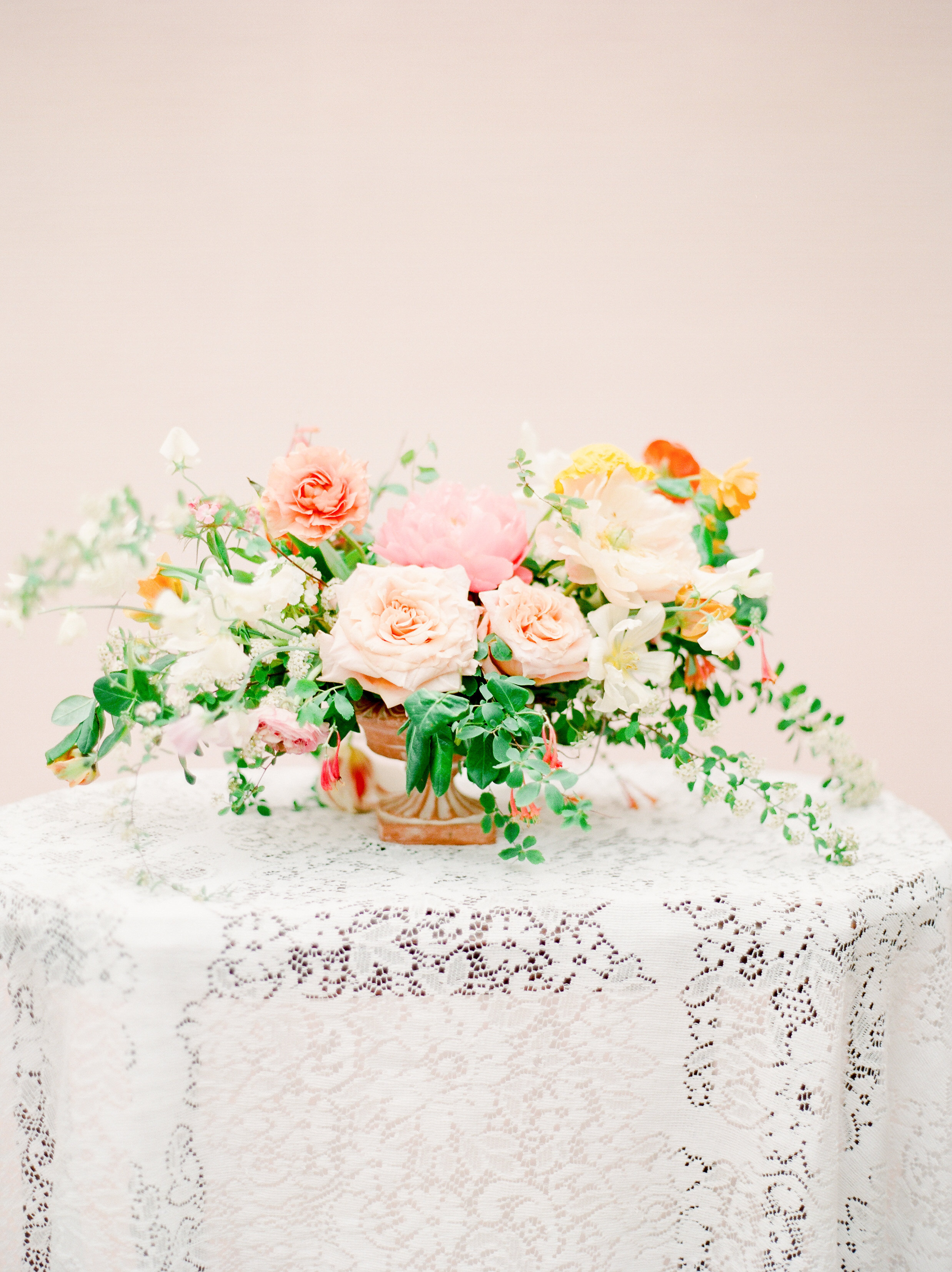 A beautiful floral arrangement paired with a lace overlay creates a beautiful welcome vignette at a wedding. Photo by  Julie Paisley . Exquisite florals by  Petal and Pine . Styling by Feather + Oak.