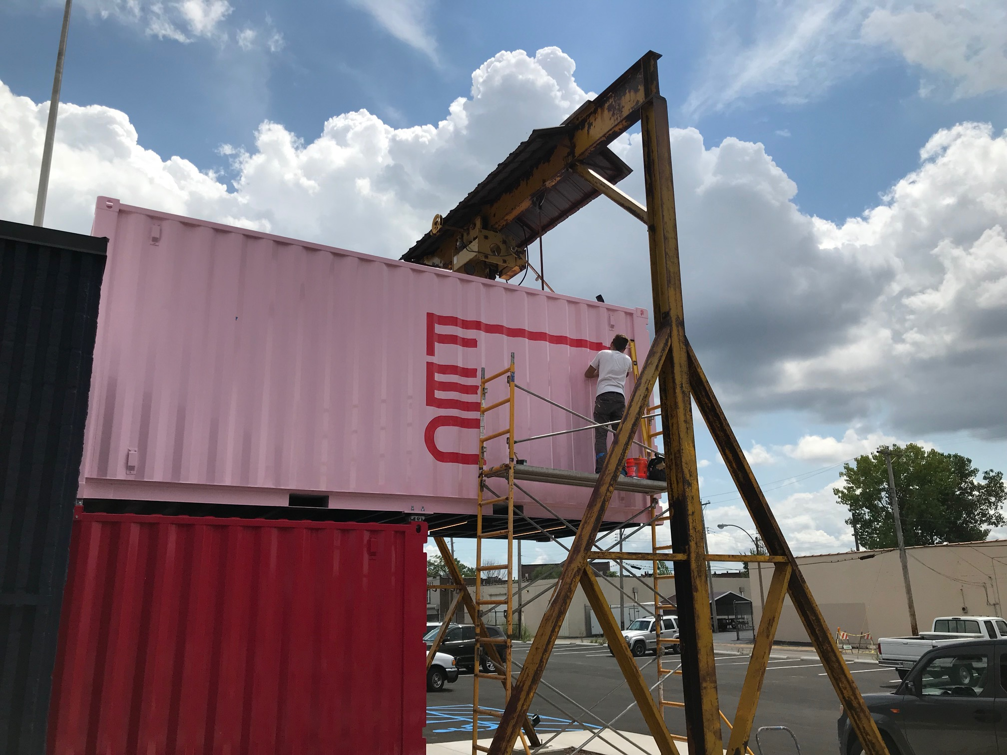 Cantilevered shipping container and gantry crane form the entrance -
