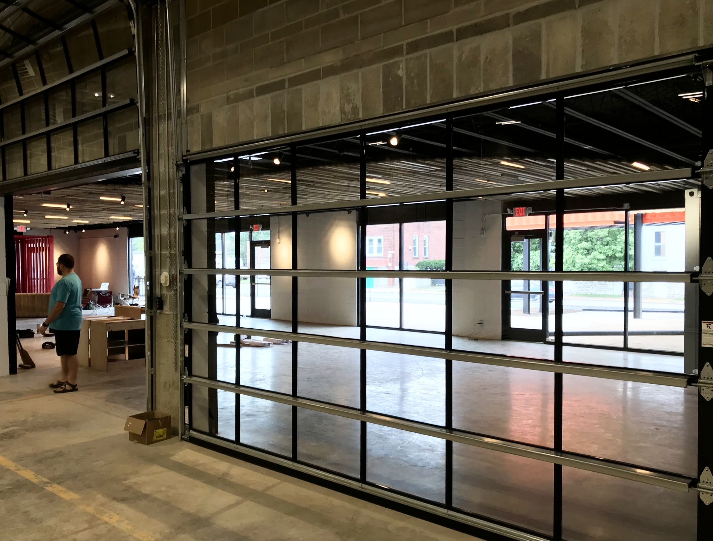 Glass garage doors open up from production area to tasting room -