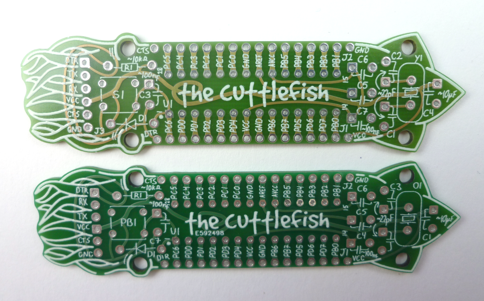 The top side of 'cuttlefish'. The bottom one is the prototype run (notice Eurocircuit's number placed inconviniently in the visual focal point of the board). The top one is the production run, where the number is placed at the bottom, with some silkscreen fixes.